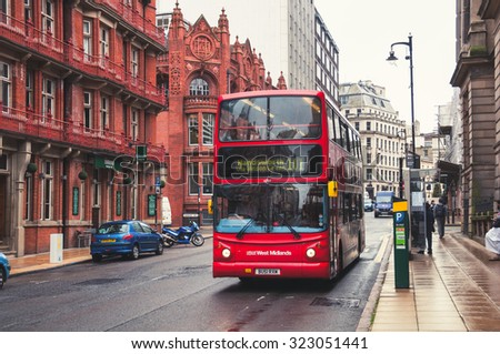 BIRMINGHAM, UK - SEPTEMBER 1, 2014: Red double-decker bus at the street. Old building of the historical part of the city. People, cars and famous restaurants and pubs - stock photo