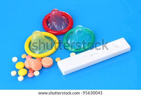 birth condoms, pregnancy test and control pills on blue background - stock photo