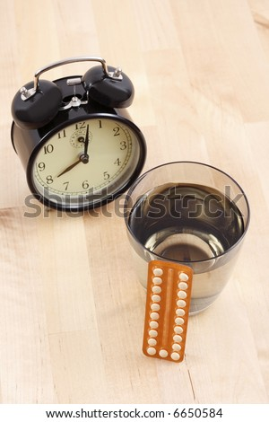 birth control pills alarm clock and glass of water - stock photo