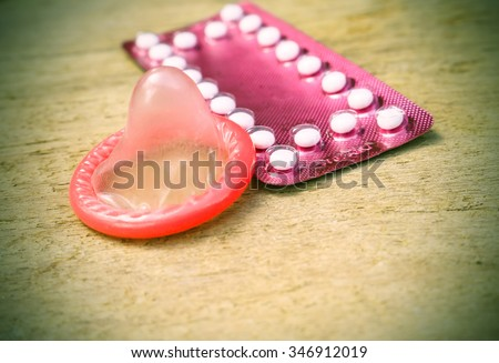 birth control pills and condom on wooden table background.soft and selective focus  vintage color tone with filter color effect. - stock photo