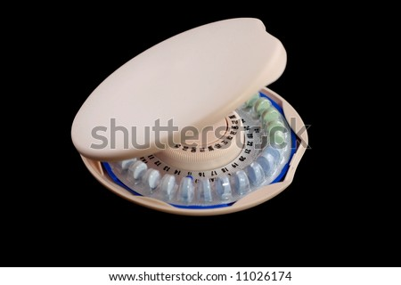 Birth Control Pills in a pink circular dispenser on a white background - stock photo