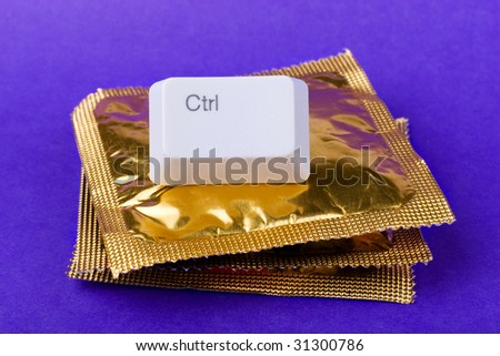 Birth rate control concept: condoms stack and ctrl keyboard key - stock photo