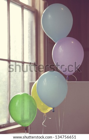 Birthday after party balloons by the old-fashioned window - stock photo