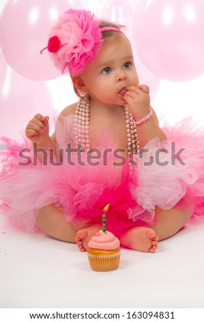Birthday baby eating her cake - stock photo