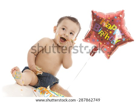 Birthday Boy!  Adorable mixed race baby boy eating a birthday cake.  Isolated on white. - stock photo