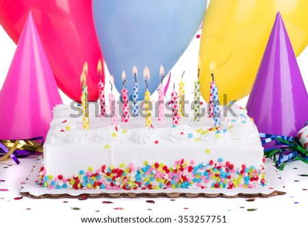 Birthday cake and burning candles with party hats and balloons