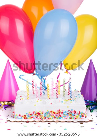 Birthday cake and candles with balloons and party hats on a white background