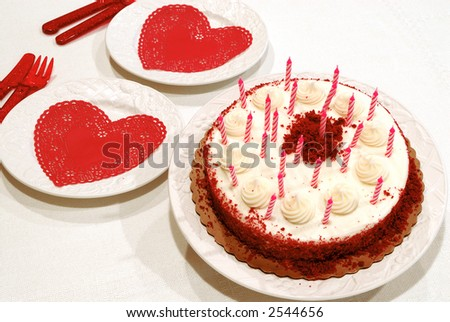 Birthday Cake and Plates - Close up of a red velvet chocolate valentine birthday cake and a slice on a plate.