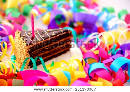 Birthday cake. Closeup top view of a piece of chocolate cake with a birthday candle decorated with confetti isolated in white background - stock photo