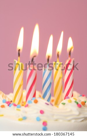 Birthday cake lit candles on pink background