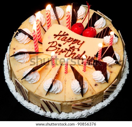 Birthday cake lit with candles. - stock photo