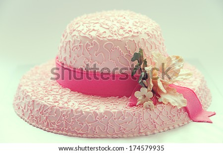 Birthday cake, looks like hat, in pink color and flower made of sugar.  - stock photo