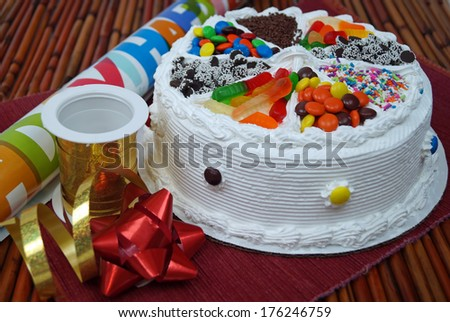 Birthday Cake, Ribbons and Bows.  A traditional birthday cake decorated with assorted candy next to party decorations wrapping paper, ribbon and a bow. - stock photo