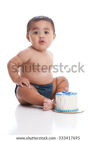 Birthday cake smash.  Adorable baby boy eating a small birthday cake.  Isolated on white.