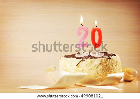 Birthday cake with burning candle as a number twenty. Focus on the candle