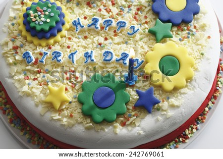 Birthday cake with burning candle, elevated view - stock photo