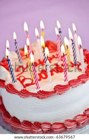 Birthday cake with burning candles and icing on pink background - stock photo