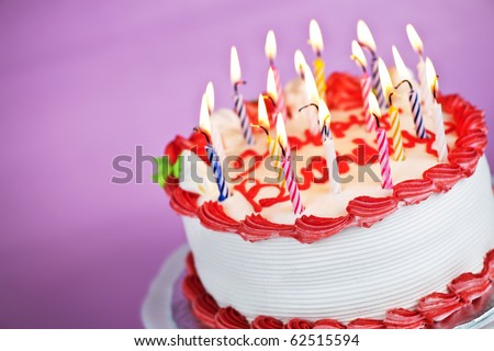 Birthday cake with burning candles on a plate on pink background - stock photo
