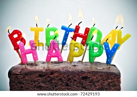 birthday cake with candles forming the sentence happy birthday - stock photo