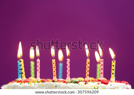 Birthday cake with candles on purple background - stock photo