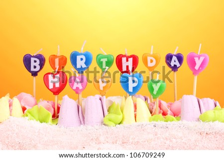 Birthday cake with candles on yellow background - stock photo