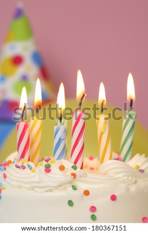 Birthday cake with colored lit candles on pink background
