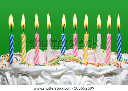 Birthday cake with colorful candles on a green background. - stock photo