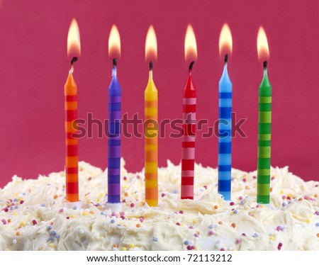 birthday cake with 6 coloured candles on a red background - stock photo