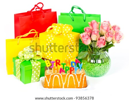 birthday cake with letter candles, flowers and gifts on white background - stock photo