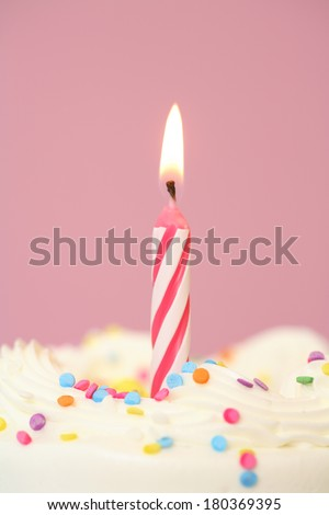 Birthday cake with lit candle on pink background - stock photo