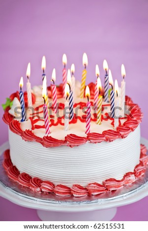 Birthday cake with lit candles and white icing - stock photo