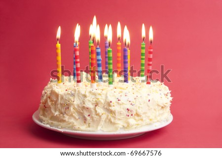 birthday cake with lots of candles on a red background - stock photo
