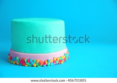 Birthday cake with sprinkles on blue background. - stock photo