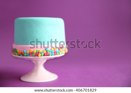 Birthday cake with sprinkles on purple background. - stock photo
