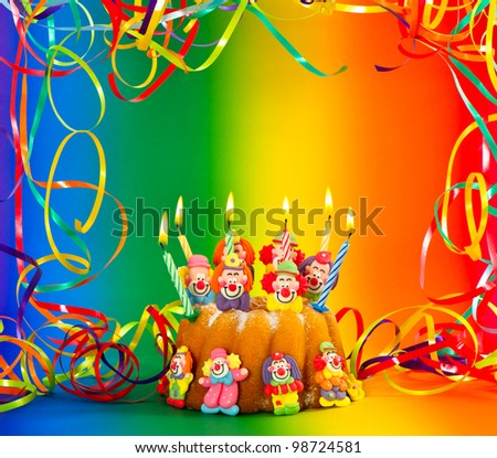 birthday cake with sugar clowns decoration and candles. colorful holidays background - stock photo