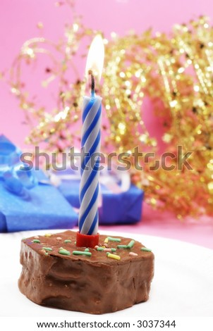Birthday candle and blue gifts on pink with gold star decorations