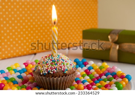 Birthday candle on a cupcake and gifts