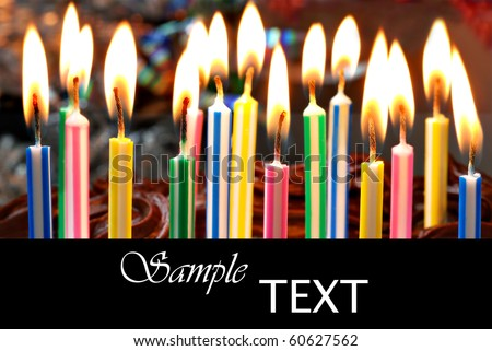 Birthday candles on chocolate cake with copy space.  Macro with shallow dof. - stock photo