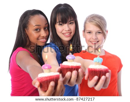 Birthday celebration with cakes for three beautiful young teenager girl friends a blonde caucasian, an oriental Japanese and an African American all with happy smiles. - stock photo