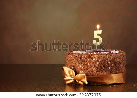 Birthday chocolate cake with burning candle as a number five on brown background - stock photo