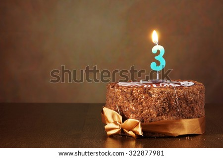 Birthday chocolate cake with burning candle as a number three on brown background - stock photo