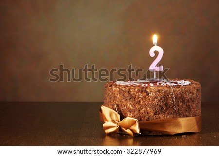 Birthday chocolate cake with burning candle as a number two on brown background - stock photo
