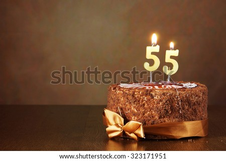 Birthday chocolate cake with burning candles as a number fifty five on brown background - stock photo
