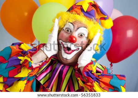 Birthday clown in full costume, looking surprised. - stock photo