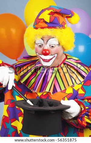 Birthday clown performing a magic act with a tophat and wand. - stock photo