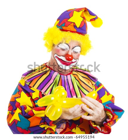 Birthday clown puts the finishing touches on a balloon animal.  Isolated on white. - stock photo