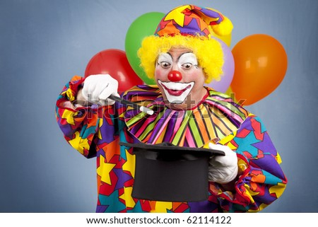Birthday clown with a top hat and wand, putting on a magic show. - stock photo