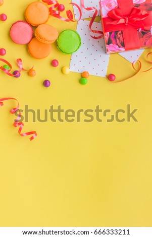 Birthday concept with wrapped gift and sweets on yellow background top view copyspace