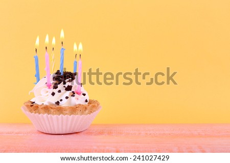 Birthday cup cake with candles on color wooden table and orange background