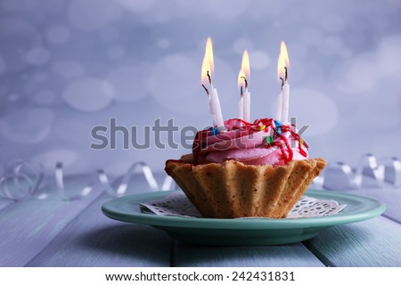 Birthday cup cake with candles on plate on color wooden table and light background - stock photo